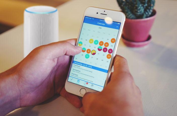 Smartphone mit Kalender und Echo (Alexa) im Hintergrund